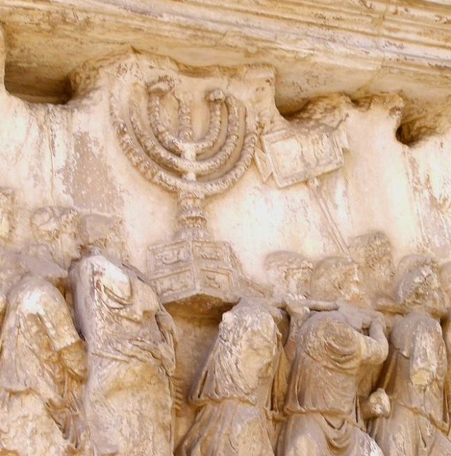 Jewish menorah, found on the inner wall of the Arch of Titus, an arch constructed in Rome by Domitian to celebrate the military victory of his brother, Titus, over the Jews. The spoils of war are displayed to commemorate the total destruction of Jerusalem and the Jewish temple there (AD 70). This photo is from Wikimedia and has been released into public domain.  Page 75, figure 39.