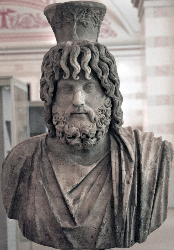 This statue represents a standard view of the Hellenistic-Egyptian deity Serapis, with a modius on his head. The modius represented a basket/measure of grain and thus bounty. The State Hermitage Museum, St. Petersburg, Russia.  © copyright holder of this work is Richard E. Oster.  Page 91, figure 50.